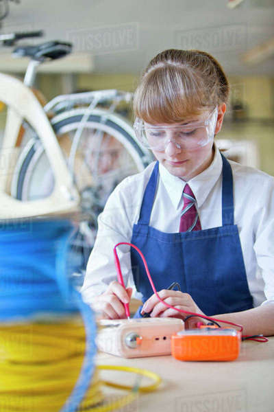 Female high school student testing electronics in shop class Royalty-free stock photo