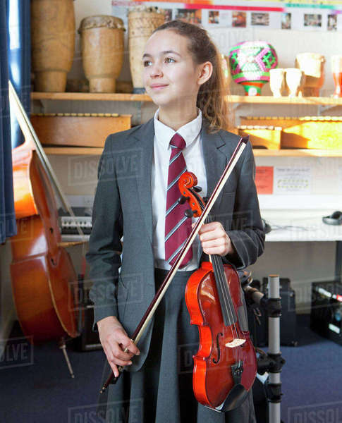 Proud high school student with violin in music classroom Royalty-free stock photo