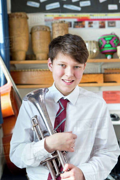 Portrait confident middle school student with trumpet in music classroom Royalty-free stock photo