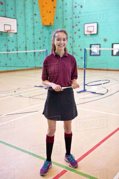 Portrait smiling high school student holding badminton racket in school gymnasium Royalty-free stock photo