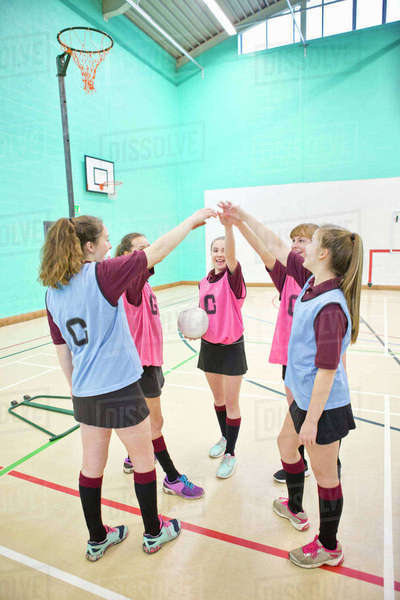 Smiling high school students touching hands in huddle before netball game Royalty-free stock photo