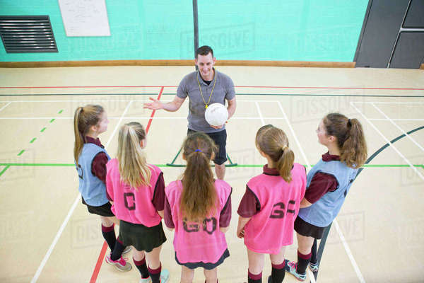 Gym teacher teaching high school students netball in gym class Royalty-free stock photo