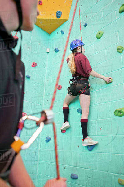 High school student holding rope supporting classmate climbing rock climbing wall Royalty-free stock photo