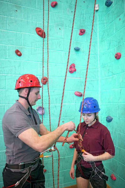 Gym teacher preparing rock climbing safety equipment for high school student Royalty-free stock photo