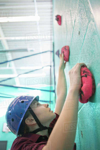 Focused high school student climbing rock climbing wall Royalty-free stock photo