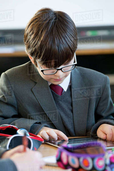 Focused middle school student doing homework with digital tablet in study hall Royalty-free stock photo