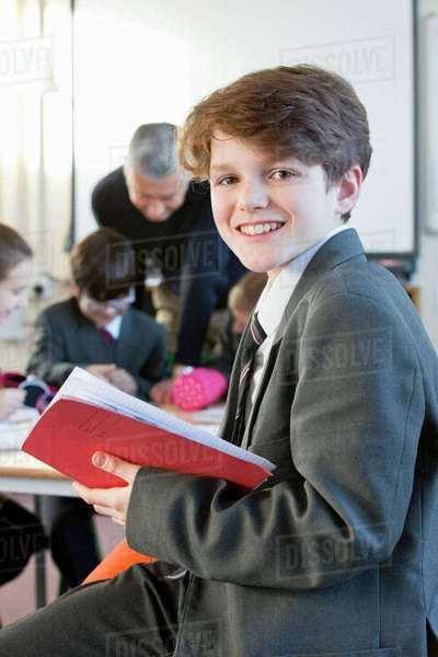 Portrait smiling middle school student with notebook in classroom Royalty-free stock photo