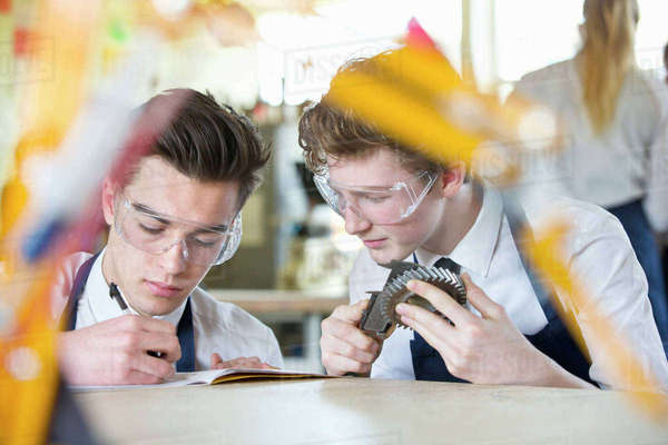 High school student measuring cog with calipers in shop class as classmate takes notes Royalty-free stock photo