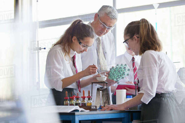 Chemistry teacher helping high school students conducting scientific experiment Royalty-free stock photo