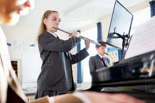 High school student playing flute behind music teacher playing piano Royalty-free stock photo
