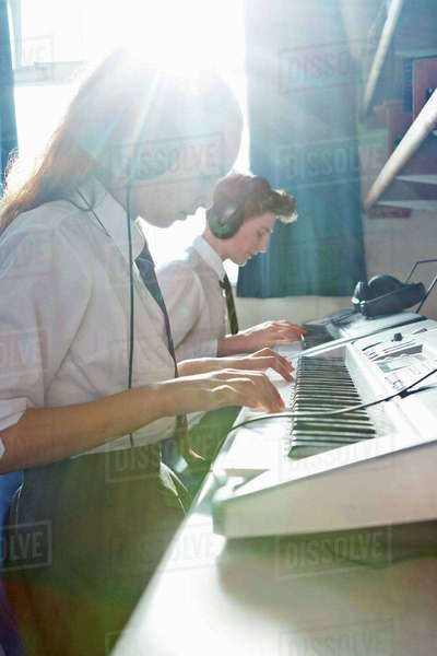 High school students playing piano in sunny music class Royalty-free stock photo