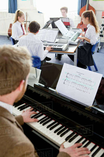 Music teacher teaching high school students playing piano in music class Royalty-free stock photo