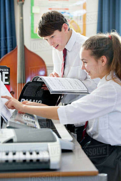 Highs school students playing piano with sheet music in music class Royalty-free stock photo