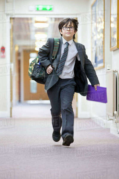 Middle school student with backpack running in school corridor Royalty-free stock photo