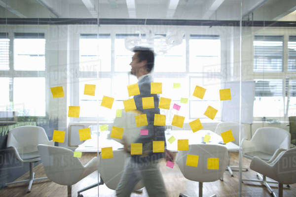 Businessman Walks Past Glass Wall Covered In Sticky Notes Royalty-free stock photo