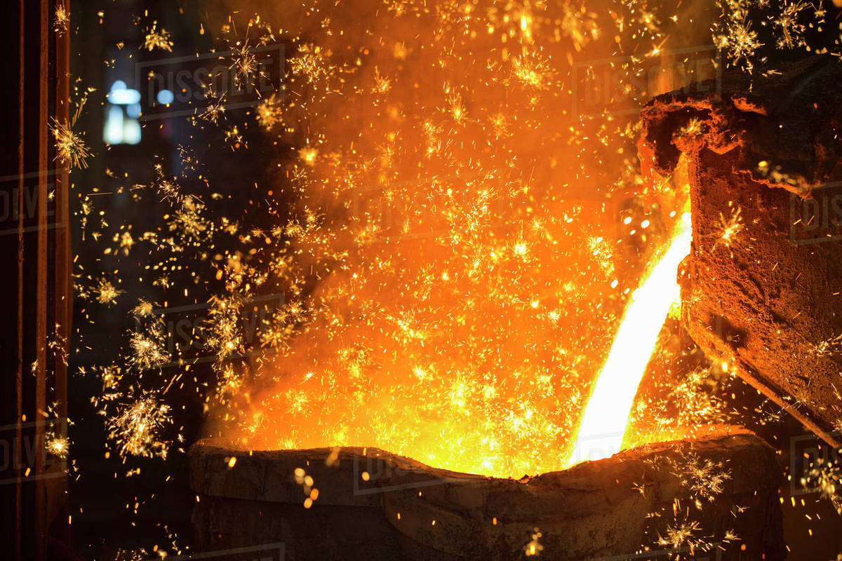 Shower of sparks as molten metal is poured in steel foundry stock photo