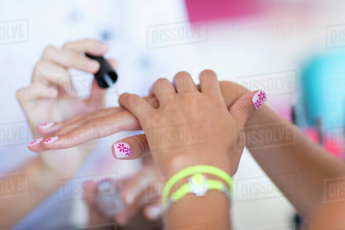 Close up of nail technician applying fingernail polish to woman\'s ...