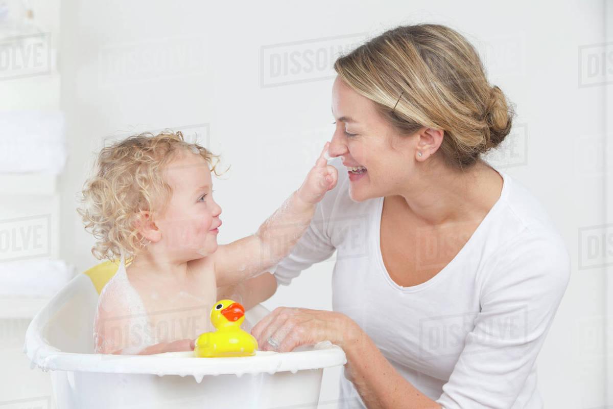 Smiling mother bathing happy baby in bathtub - Stock Photo - Dissolve