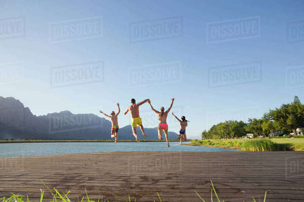 Family jumping into lake from a jetty Royalty-free stock photo