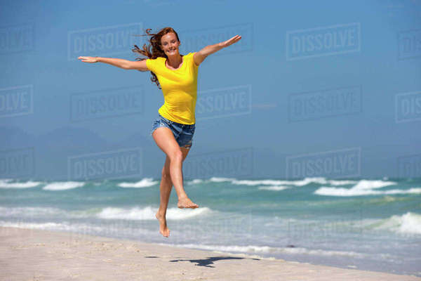 Happy woman, with arms outstretched, leaping in air on sunny beach Royalty-free stock photo