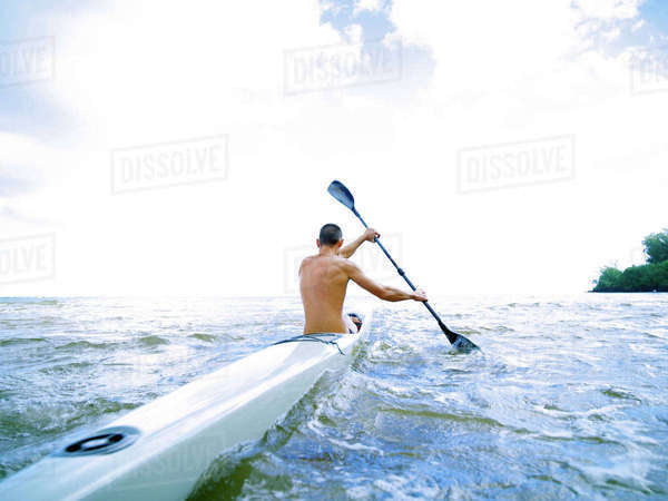 Hawaii, Kauai, Anini Beach, Active Male Paddling In A One Man Canoe. Rights-managed stock photo