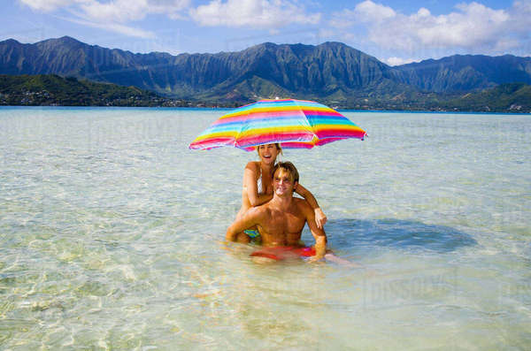 Hawaii, Oahu, Kaneohe, Couple Under A Brightly Colored Umbrella In Crystal Clear Water At The Sandbar Or Dissapearing Island Rights-managed stock photo