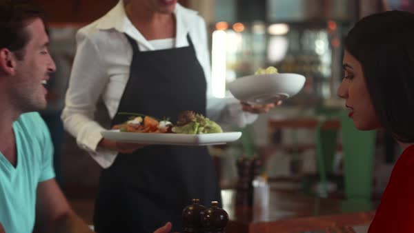 Waitress serving food to couple at cafe. Royalty-free stock video