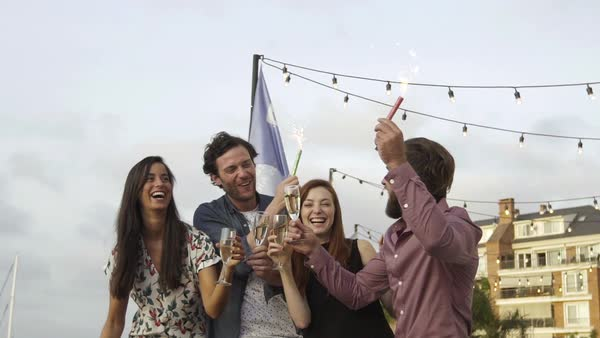 Group of friends celebrating outdoors with champagne and sparklers Royalty-free stock video