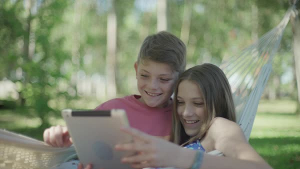 Children in hammock using digital tablet together Royalty-free stock video