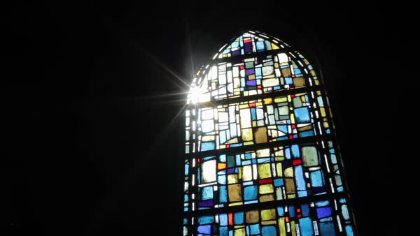 Dolly shot of sunlight shining through a stained glass window Royalty-free stock video