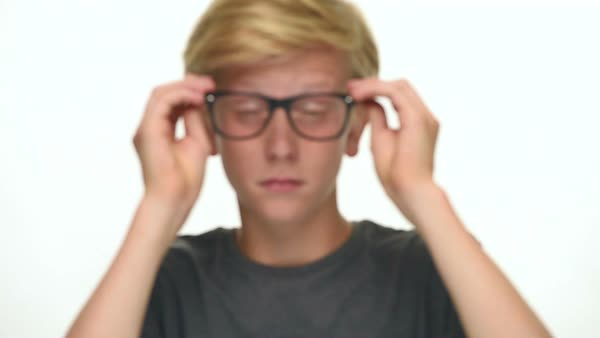 Blond Teenager Student Boy With Black Glasses Tries To Focus Looking At Camera Isolated On White