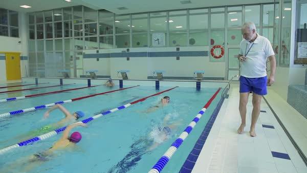 tracking shot of school children practicing crawl stroke in indoor