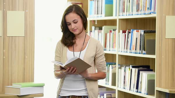 Young female student reading book in college library Royalty-free stock video