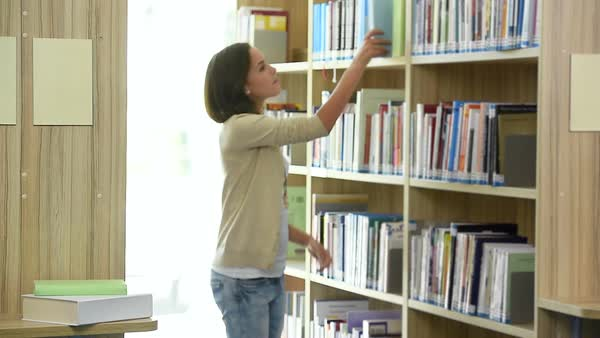 Student girl searching and finding book in school library Royalty-free stock video