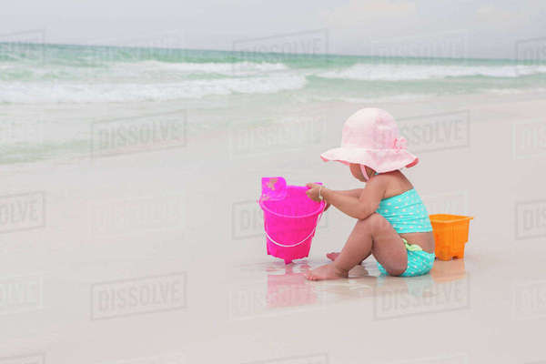 Toddler Girl Playing with Shovel and Bucket in Sand on Beach, Destin, Florida, USA Royalty-free stock photo