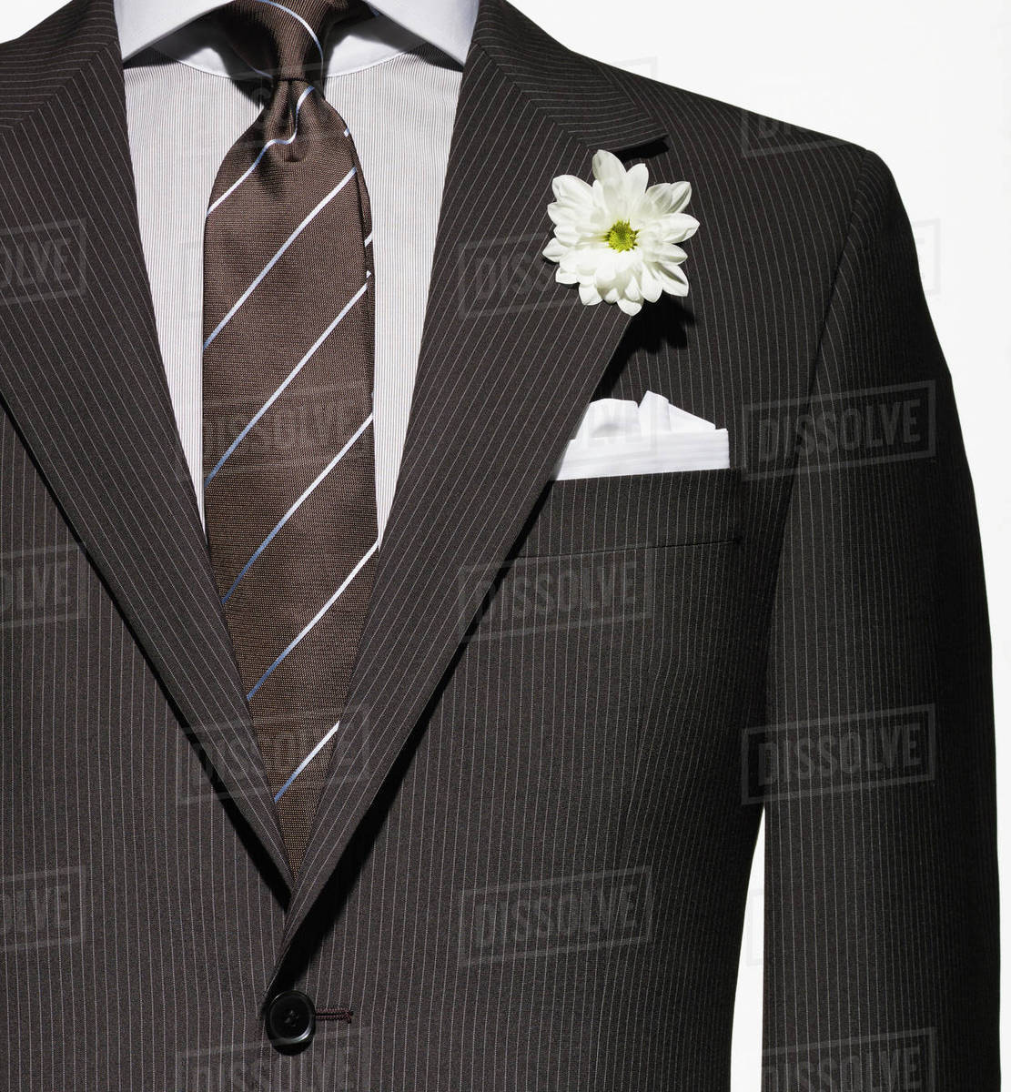 b274a00e43587 Detail of a brown suit jacket with shirt and necktie, and white handkerchief  and flower
