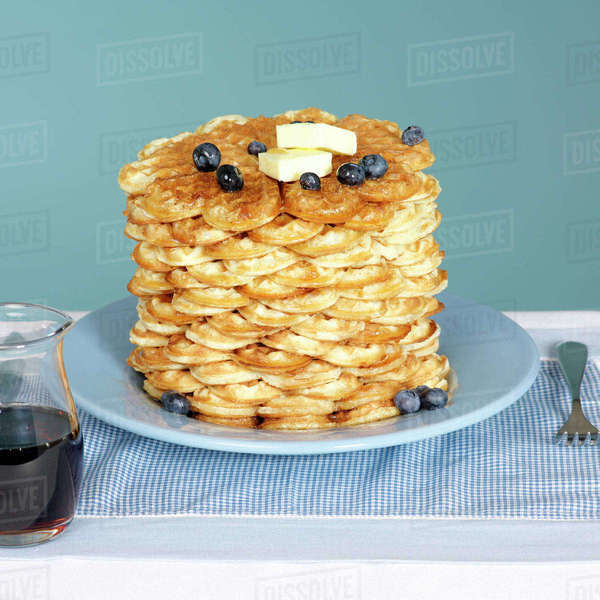 Stack of Waffles on Blue Plate with Butter and Blueberries and Maple Syrup in Jug on the Side Royalty-free stock photo