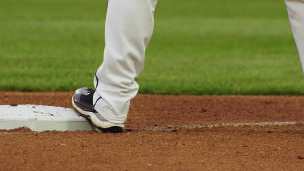 Extreme close up of a baseball player's foot on third base, preparing to run. Royalty-free stock video