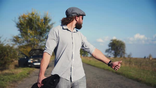 Man in grey cap with beard and ponytail hitchhiking, taking off cap and looking at watch. Royalty-free stock video