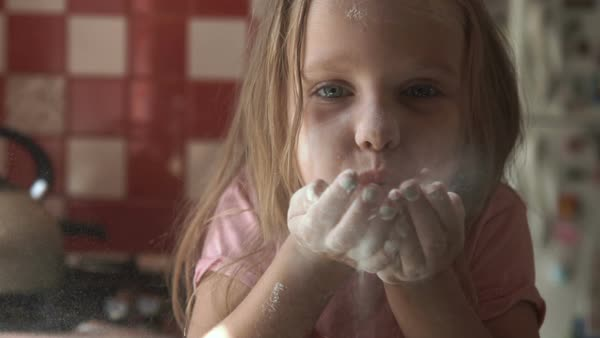 Young girl blowing flour from hands in kitchen Royalty-free stock video