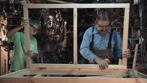 Carpenter with grandson making window frame Royalty-free stock video
