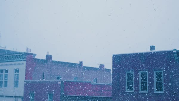 Snow falls overlooking the rooftops of historic downtown. Royalty-free stock video