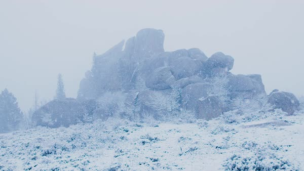 Snow falls upon a rock formation. Royalty-free stock video