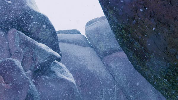 Looking up at large rock structure as snow drifts down. Royalty-free stock video