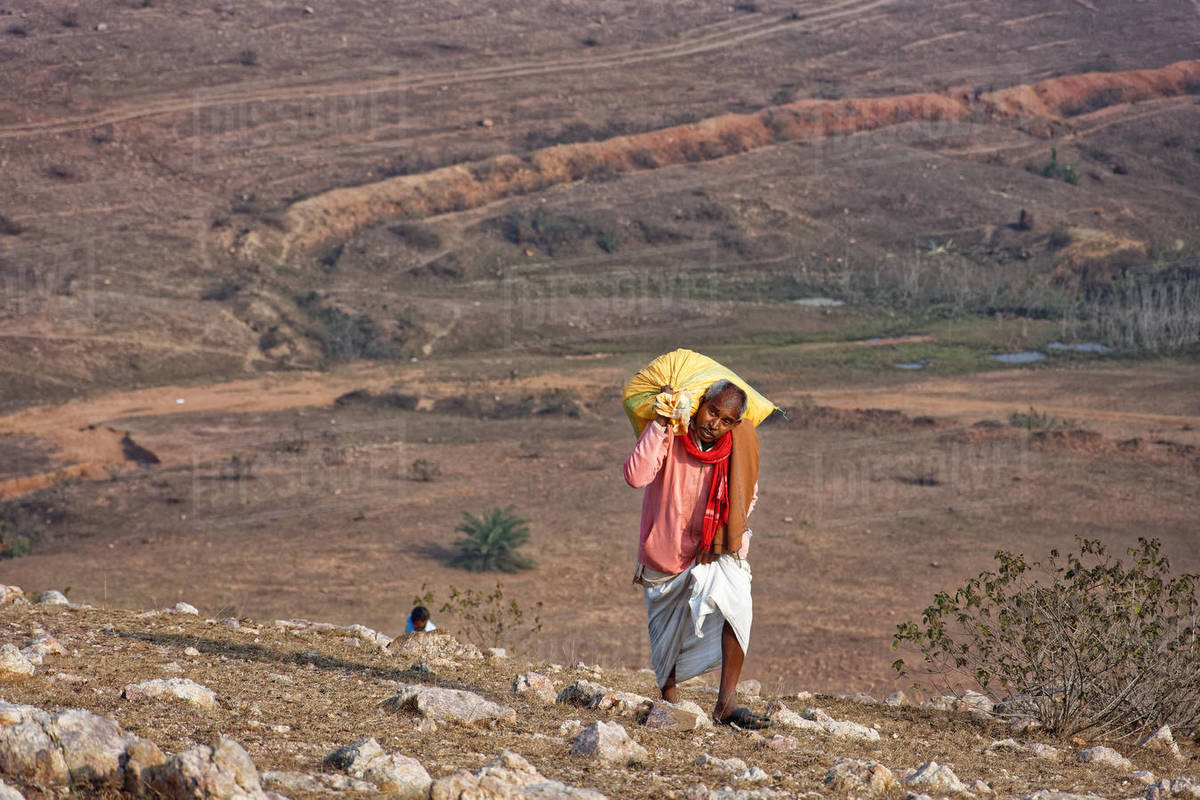 Indian old rural businessman climbing while carrying goods on hilltop. Royalty-free stock photo