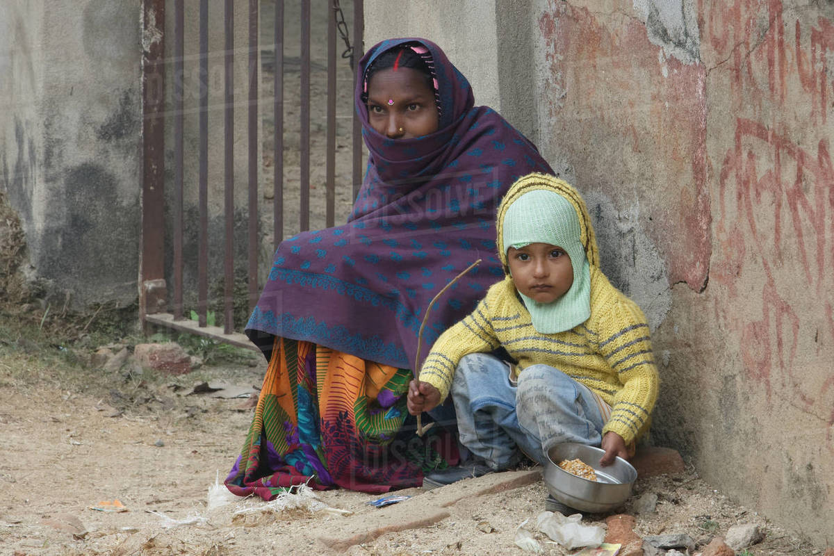 Mother and infant boy child is sitting on road in winter morning Royalty-free stock photo