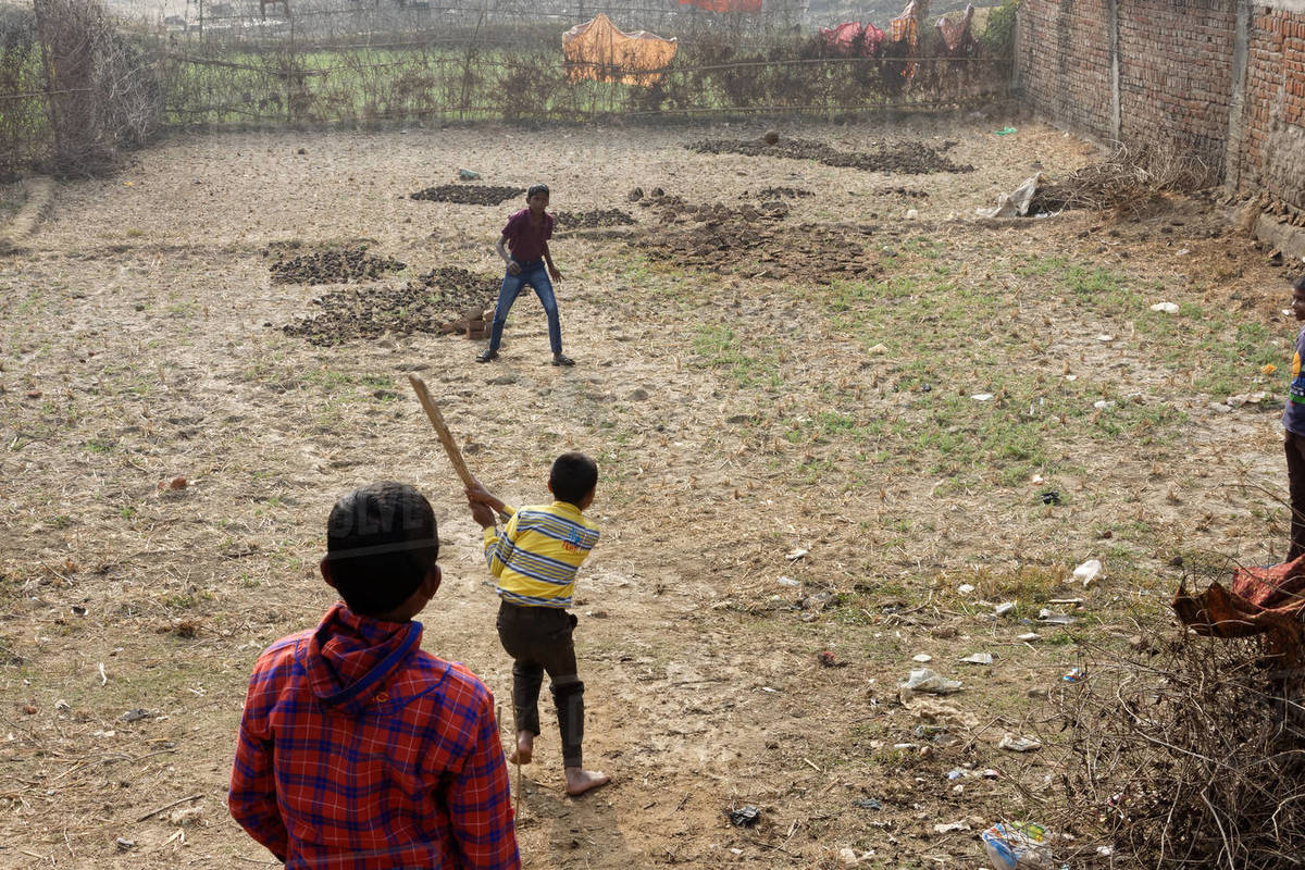 Three little Indian rural boys are playing cricket on farmer's land Royalty-free stock photo