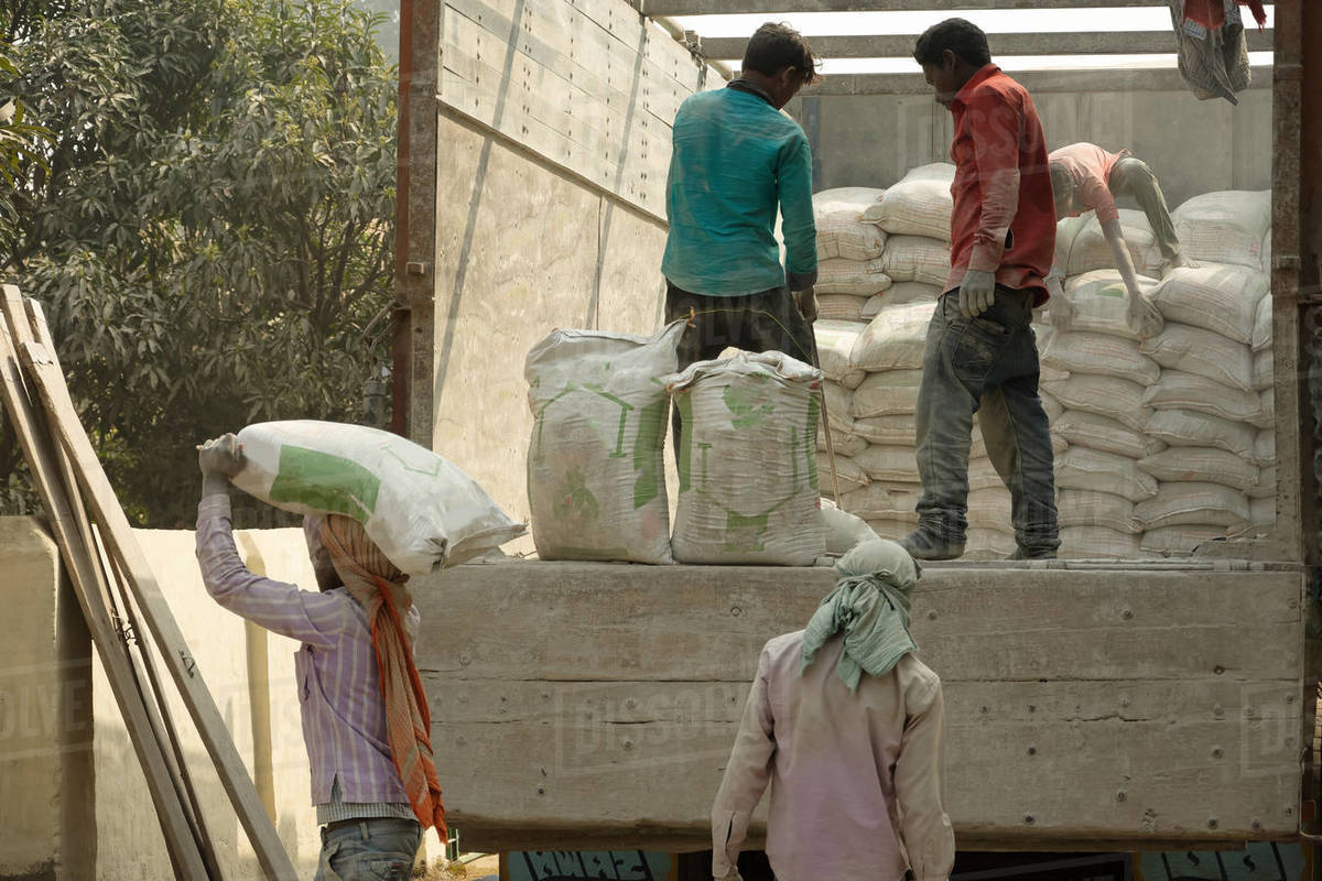 A group of labors are transporting cement from the back of a truck Royalty-free stock photo
