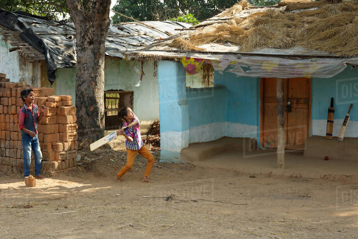 Indian little local boys are playing cricket near hut house Royalty-free stock photo