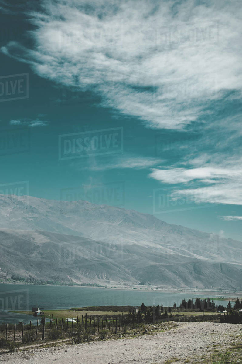 Vertical shoot of a road to lake on a backdrop of mountains. Royalty-free stock photo
